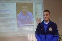 Paul Turnball stood next to projection of Stockport County Football Club Website